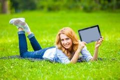 Mulher bonita que encontra-se na grama com tabuleta Fotos de Stock