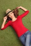 Mulher bonita que encontra-se na grama em um prado Fotografia de Stock Royalty Free