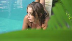 Mulher bonita que encontra-se na piscina em f?rias de ver?o na est?ncia Jovem mulher que relaxa perto da piscina em ensolarado filme