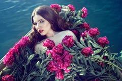 Mulher bonita que encontra-se no barco de madeira coberto com a pilha enorme das peônias fotos de stock royalty free