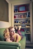 Mulher bonita que encontra-se no sofá Fotografia de Stock Royalty Free