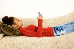 Mulher bonita que encontra-se no sofá com telefone esperto foto de stock