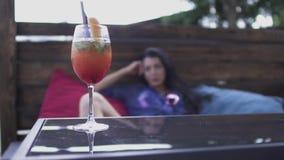 Mulher bonita que encontra-se nos descansos no café moderno no fundo do vidro de cocktail A morena de encantamento relaxa na vídeos de arquivo