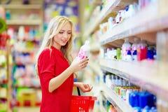 Mulher bonita que escolhe o produto dos cuidados pessoais no supermercado Fotografia de Stock