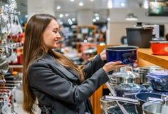Mulher bonita que escolhe pratos do utensílio em um supermercado da loja fotografia de stock
