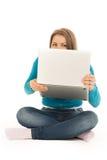 Mulher bonita que esconde atrás de um portátil Fotografia de Stock