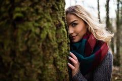 Mulher bonita que esconde atrás do tronco de árvore na floresta Fotografia de Stock