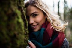 Mulher bonita que esconde atrás do tronco de árvore na floresta Fotos de Stock Royalty Free