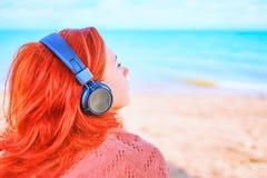 Mulher bonita que escuta a música na praia imagem de stock