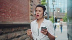 Mulher bonita que escuta a música no fones de ouvido que canta usando o smartphone fora video estoque