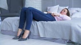 Mulher bonita que esforça-se para fechar suas calças de brim na cama vídeos de arquivo