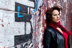 Mulher bonita que espera na parede dos grafittis Fotografia de Stock