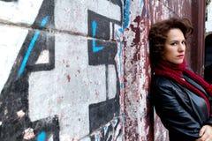 Mulher bonita que espera na parede dos grafittis Fotos de Stock