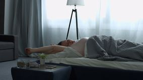 A mulher bonita que estica na cama após acorda video estoque