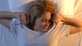Mulher bonita que estica na cama confortável, luz solar da manhã fora da janela filme
