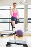 Mulher bonita que executa o exercício da ginástica aeróbica da etapa Fotografia de Stock