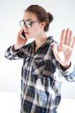Mulher bonita que fala no telefone celular e que mostra o gesto da parada Imagem de Stock