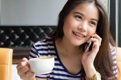 Mulher bonita que fala no telefone e que guarda a xícara de café Imagem de Stock