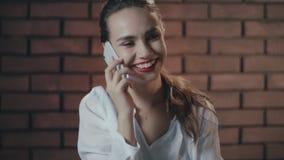 Mulher bonita que fala o telefone esperto e que sorri no fundo da parede de tijolo video estoque