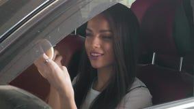 Mulher bonita que faz a composição no carro da classe executiva com cadeiras vermelhas Imagem de Stock