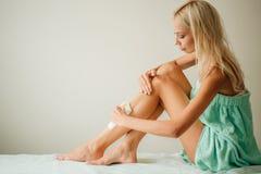Mulher bonita que faz a depilação para seus pés com enceramento da tira Imagem de Stock