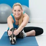 Mulher bonita que faz esticando exercícios Fotografia de Stock