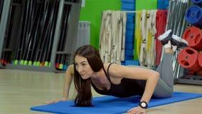 Mulher bonita que faz impulso-UPS na esteira do exercício no salão da aptidão foto de stock royalty free