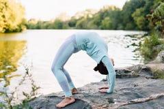 A mulher bonita que faz a ioga exercita no parque Fotografia de Stock