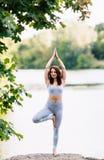 A mulher bonita que faz a ioga exercita no parque Fotografia de Stock Royalty Free