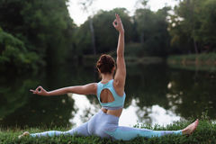 A mulher bonita que faz a ioga exercita no parque Imagem de Stock Royalty Free