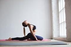 A mulher bonita que faz o esticão exercita no gym foto de stock