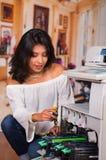 Mulher bonita que fixa uma fotocopiadora e que sorri durante a manutenção usando uma chave de fenda Imagem de Stock Royalty Free