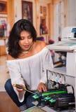 Mulher bonita que fixa uma fotocopiadora e que sorri durante a manutenção usando uma chave de fenda Fotografia de Stock