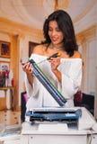 Mulher bonita que fixa uma fotocopiadora e que sorri durante a manutenção usando uma chave de fenda Fotografia de Stock Royalty Free