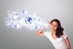 Mulher bonita que gesticula com ícones sociais da rede Foto de Stock