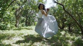 A mulher bonita que guarda a corrida disponivel da maçã através de um jardim, neva o conto de fadas branco filme