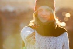 Mulher bonita que guarda a decoração vermelha do Natal no por do sol Fotografia de Stock