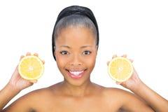 Mulher bonita que guarda fatias de laranja e que olha a câmera Foto de Stock