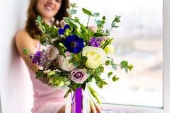 Mulher bonita que guarda o ramalhete das flores Fotos de Stock