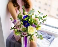 Mulher bonita que guarda o ramalhete das flores Fotografia de Stock