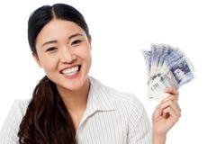 Mulher bonita que guarda um fã de notas da moeda Foto de Stock