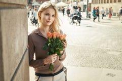 Mulher bonita que guarda um ramalhete colorido das flores Fotografia de Stock
