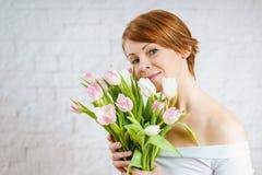 Mulher bonita que guarda um ramalhete das tulipas Fotografia de Stock Royalty Free