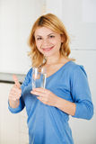 A mulher bonita que guarda um vidro da água e que mostra manuseia acima de s Imagens de Stock