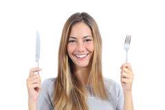 Mulher bonita que guarda uma forquilha e uma faca de tabela Foto de Stock