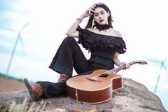 Mulher bonita que guarda uma guitarra imagens de stock royalty free