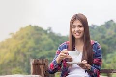A mulher bonita que guarda uma xícara de café, o fundo é um bea imagens de stock