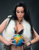 Mulher bonita que guardara um globo imagem de stock