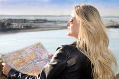 Mulher bonita que guardara um mapa Fotografia de Stock
