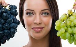 Mulher bonita que guardara uvas frescas Fotografia de Stock